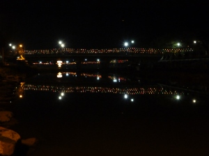 If you look carefully, you can see hundreds of bamboo lanterns, each with a coloured light inside, strung above the bridge across the river, all reflected in the water below.
